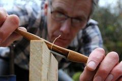 使用古色古香的黄杨木潜叶虫辐刀的传统木工 免版税库存照片
