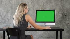 使用台式电脑的女实业家在创造性的办公室 绿色屏幕大模型显示 股票录像