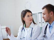 使用台式计算机的医生,当谈论治疗时新的方式  图库摄影