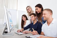 使用台式计算机的微笑的买卖人 免版税图库摄影