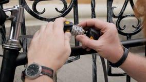 使用号码锁和链子的年轻人特写镜头4k英尺长度保护他的在街道上的自行车 影视素材
