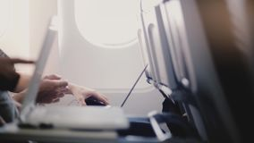 使用各种各样的移动设备、智能手机和屏幕膝上型计算机的平面乘客特写镜头侧视图在飞行期间 股票视频