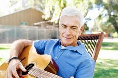 使用吉他的老人户外 图库摄影