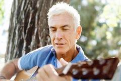 使用吉他的老人户外 库存图片