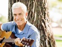使用吉他的老人户外 免版税库存照片
