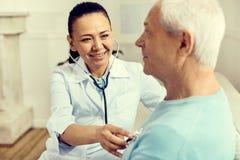 使用听诊器的光芒四射的女性护士,当检查肺时 免版税库存照片