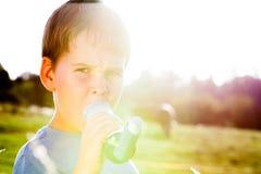使用吸入器的男孩为哮喘在牧场地 图库摄影