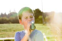 使用吸入器的男孩为哮喘在牧场地 库存图片