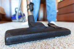 使用吸尘器刷子的妇女的播种的图象,当清洗一张米黄地毯时 免版税库存图片