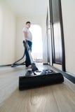 使用吸尘器的孩子在房子里 免版税库存图片