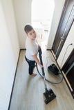 使用吸尘器的孩子在房子里 图库摄影