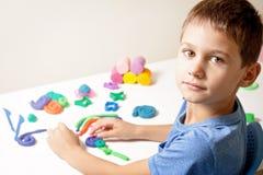 使用和创造从雕塑黏土或彩色塑泥的男孩在白色桌上 免版税库存照片