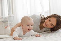 使用和微笑在床上的母亲和婴孩 免版税图库摄影