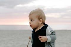 使用和探索在沙子的逗人喜爱的矮小的男婴孩子画象在海滩在日落外部期间在度假在有冠乌鸦的 免版税库存图片