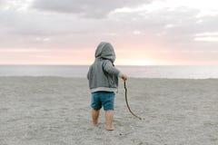使用和探索在沙子的逗人喜爱的矮小的男婴孩子画象在海滩在日落外部期间在度假在有冠乌鸦的 免版税库存照片