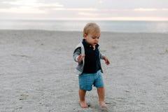 使用和探索在沙子的逗人喜爱的矮小的男婴孩子画象在海滩在日落外部期间在度假在有冠乌鸦的 库存图片