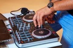 使用和控制音乐的专业音乐设备在夜总会用手DJ 免版税图库摄影