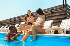 使用和放松在游泳池的小组朋友在暑假期间 库存图片
