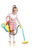 使用和有玩具吸尘器的儿童女孩洁净室 库存图片