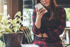 使用和看充满感觉的一名美丽的亚裔妇女巧妙的电话乏味,当等待某人在现代绿色咖啡馆时 库存照片