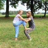使用和站立在彼此的两个女孩 图库摄影
