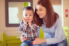 使用和笑与她的小儿子的年轻俏丽的母亲 免版税库存照片