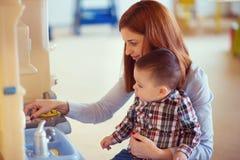 使用和笑与她的小儿子的年轻俏丽的母亲 免版税库存图片