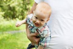 使用和笑与爸爸的微笑的男婴 免版税库存照片
