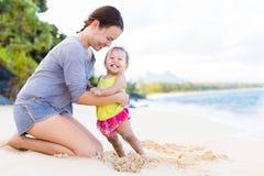 使用和笑在海滩岸的母亲和孩子 图库摄影
