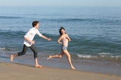 使用和跑在海滩的夫妇 免版税库存照片
