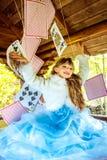 使用和跳舞与在桌上的大纸牌的一个小美丽的女孩 免版税图库摄影