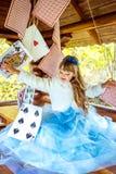 使用和跳舞与在桌上的大纸牌的一个小美丽的女孩 免版税库存照片