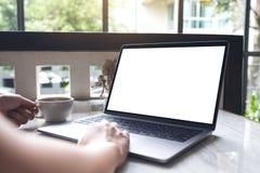 使用和输入在有空白的白色屏幕的膝上型计算机的妇女,当喝咖啡现代咖啡馆时 免版税库存照片