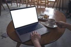 使用和输入在有空白的白色屏幕的膝上型计算机的妇女,当喝咖啡现代咖啡馆时 库存照片