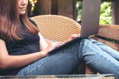 使用和键入在膝上型计算机键盘的亚裔妇女,当坐室外充满放松时的感觉 库存图片