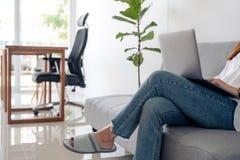 使用和键入在膝上型计算机键盘的妇女,当坐有感觉的沙发放松时 库存照片