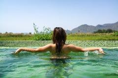 使用和飞溅在游泳池的亚裔妇女 库存图片
