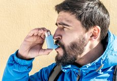 使用哮喘吸入器的画象人室外 库存图片