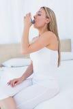 使用哮喘吸入器的秀丽金发碧眼的女人 库存图片
