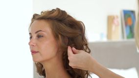 使用喷发剂的美发师,当创造卷曲发型对长发妇女时 做卷曲的头发的发式专家 股票录像