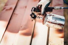 使用喷枪的工作者为应用在木材的棕色油漆 免版税图库摄影