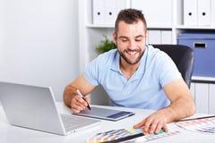 使用图形输入板的图表设计师在一个现代办公室 免版税库存照片