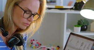 使用图形输入板的白种人女性时尚编辑侧视图在书桌在办公室4k 股票录像