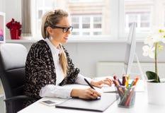 使用图形输入板的年轻女性设计师,当与计算机一起使用时 库存图片
