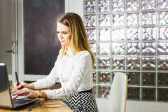 使用图形输入板的年轻女性设计师,当与计算机一起使用时 免版税图库摄影