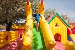 使用在一个可膨胀的玩具房子里的年轻男孩在公园 图库摄影