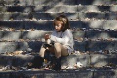 使用在一个城市公园的小女孩在秋天 免版税库存图片