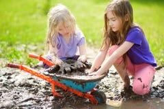 使用在一个大湿泥浆坑的两个滑稽的小女孩在晴朗的夏日 得到的孩子肮脏,当开掘在泥泞的土壤时 免版税库存图片