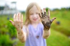 使用在一个大湿泥浆坑的滑稽的小女孩在晴朗的夏日 得到的孩子肮脏,当开掘在泥泞的土壤时 免版税库存图片