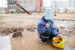 使用在一个泥泞的水坑的男孩 库存照片